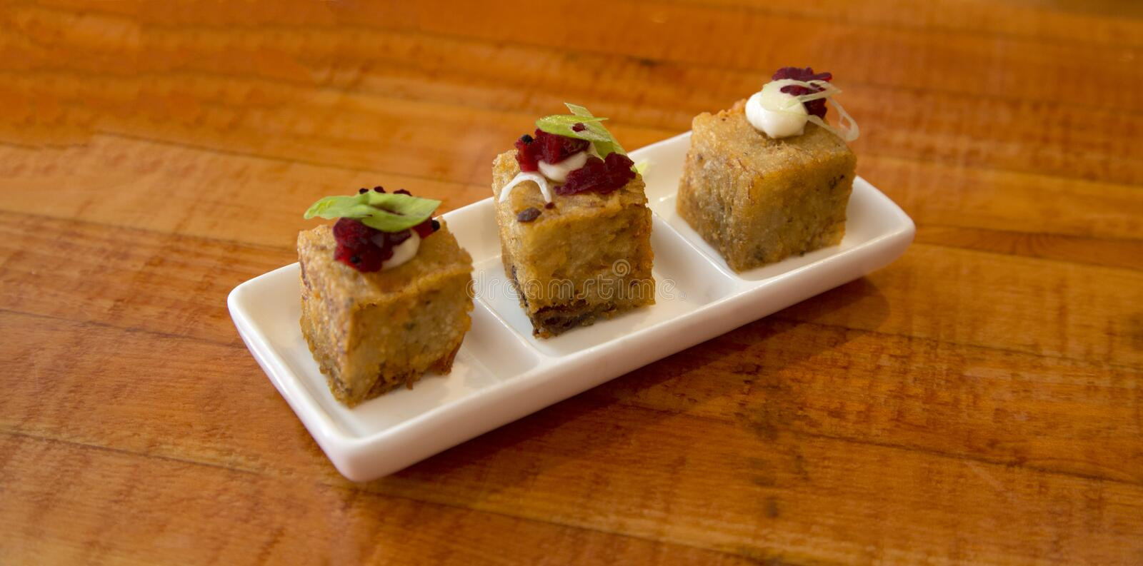 Small potato and ham bites with red beet relish and aioli stock images