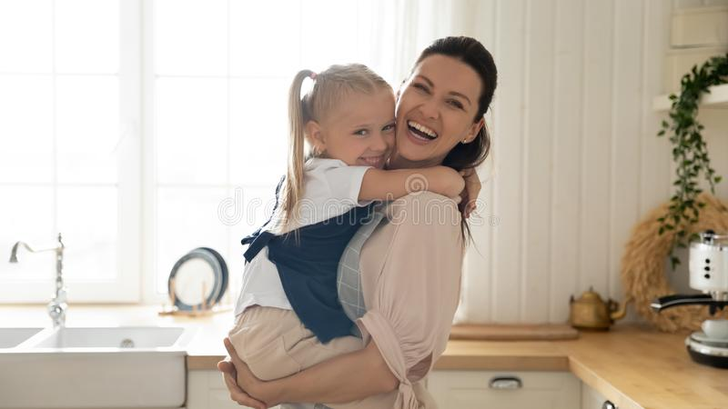 Happy mother holding on hands adorable preschool daughter in kitchen. Small preschool cute girl smiling looking at camera on mother hands in kitchen at home royalty free stock image