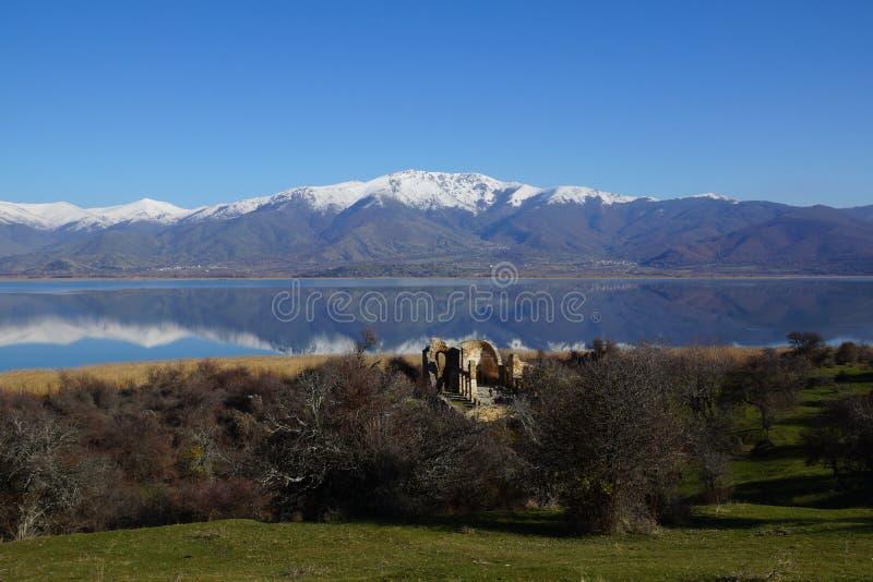 Small Prespa Lake, Agios Achillios island, the ruins of St. Achillius, Greece. Picturesque Small Prespa Lake with surrounding mountains, Agios Achillios island stock images