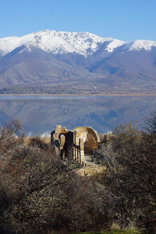 Small Prespa Lake, Agios Achillios island, the ruins of St. Achillius, Greece. Picturesque Small Prespa Lake with surrounding mountains, Agios Achillios island stock photography
