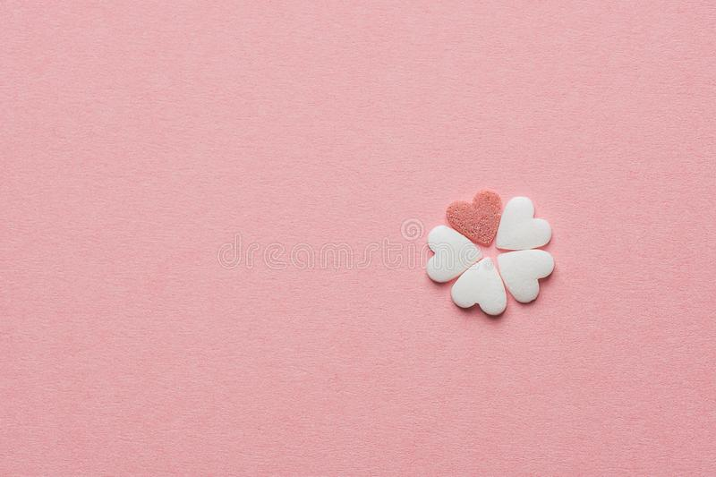 Small Pretty Flower Made of Heart Shape Sugar Candy White and Red Sprinkles on Pastel Pink Background. Valentines Mother`s Day. Kids Charity Creativity Concept stock images