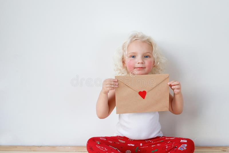 Small pretty girl with curly hair, rouge cheeks, dressed casually, sits crossed legs, holds mysterious letter in hands royalty free stock photography