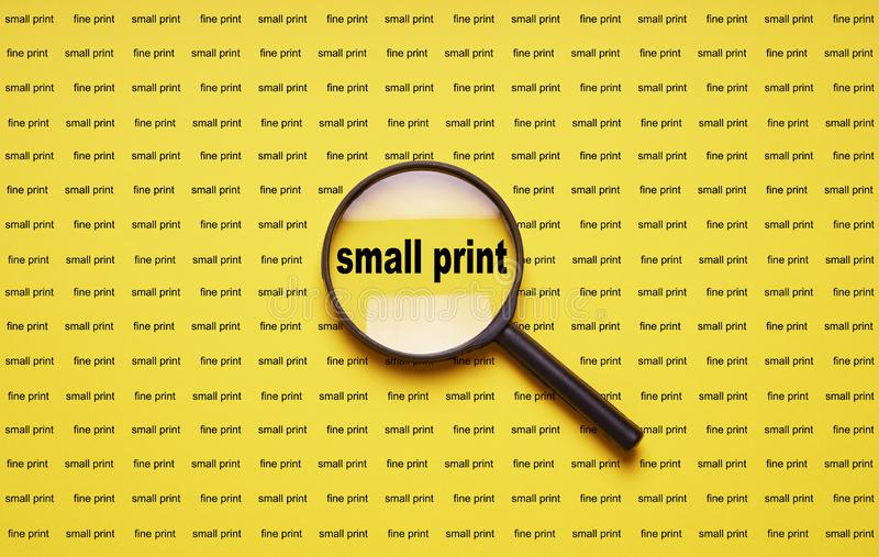 Small print enlarged with magnifying glass magnifier loupe royalty free stock images