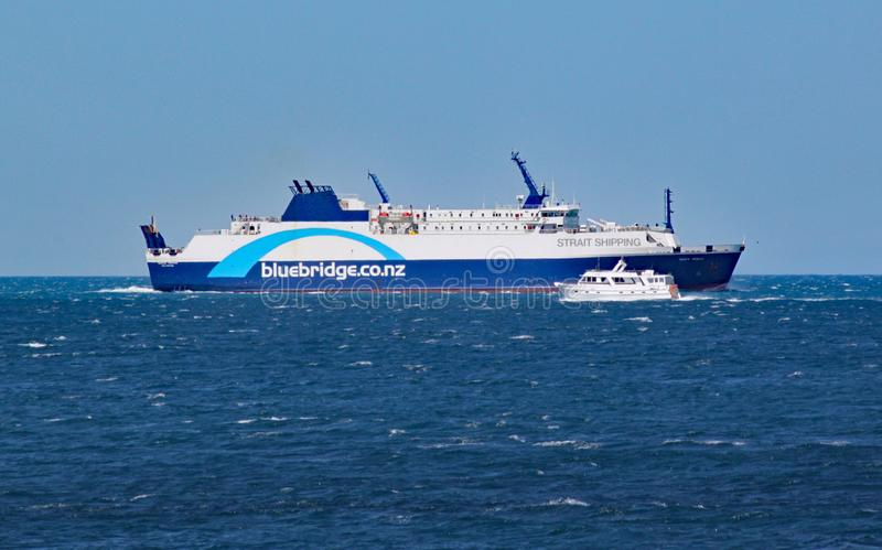A small private motor boat crosses by an Interislander ferry on the Cook Strait stock images
