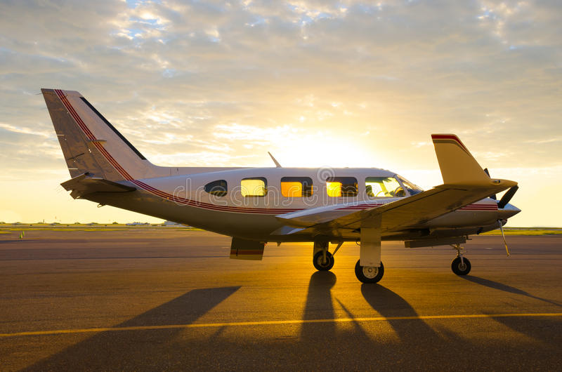 Small private propeller passenger piper plane. A private company turbo prop propeller passenger piper plane is on the tarmac at sunrise with dramatic lighting royalty free stock images