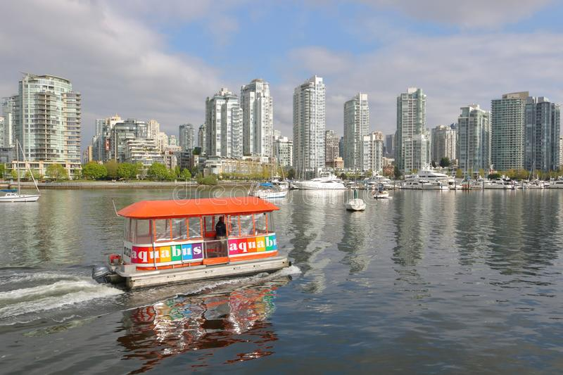 Public Ferry and Downtown Vancouver, Canada. A small public ferry, a legacy from Vancouver, Canada`s Expo `86 era, crosses False Creek near the downtown core on royalty free stock images