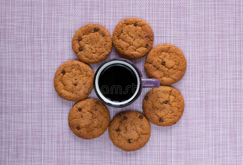 A small purple cup of coffee and mouth-watering avatina cookies with chocolate crumb. On a pink napkin royalty free stock photos