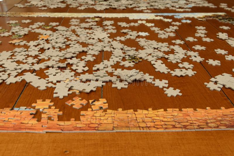 Small puzzle pieces are strewn across a table top. stock image