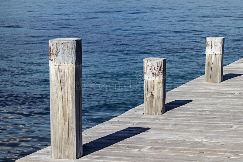 A small quay and its three square mooring poles that create geometric games with the shadows and the symmetry of the wooden planks. Of the quay on the blue sea stock images