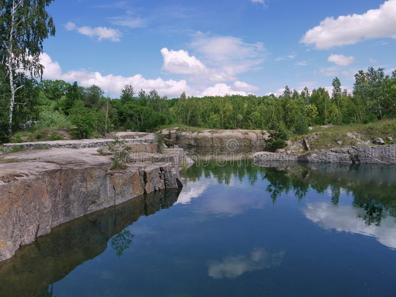 A small quiet pond with clear water lying between the stone banks. For your design stock image