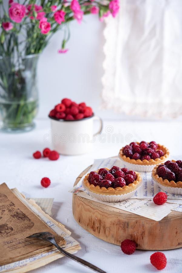 Small raspberry tarts on bright background royalty free stock photography