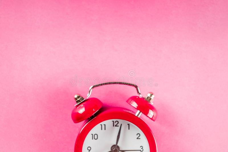 Small red alarm clock on bright pink table. Performance, work or study concept, Creative flatlay copy space above stock images