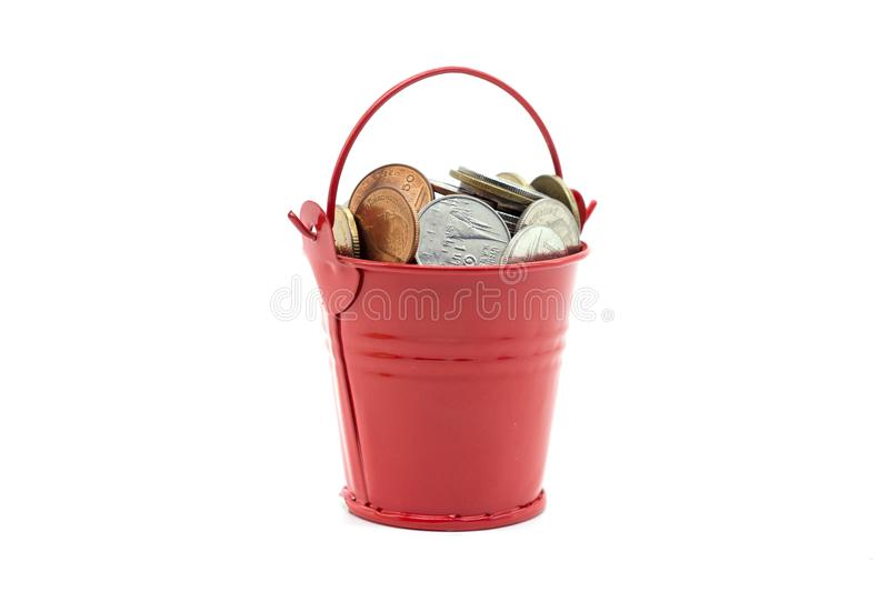 Small red bucket full of money on white background.  royalty free stock photo