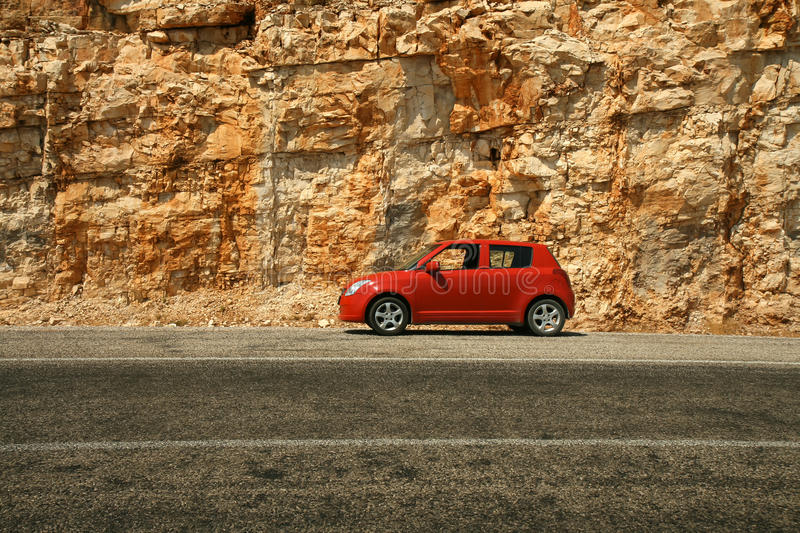 Small red car against a background of a rock. Small red car against a background of a vertical rock royalty free stock images