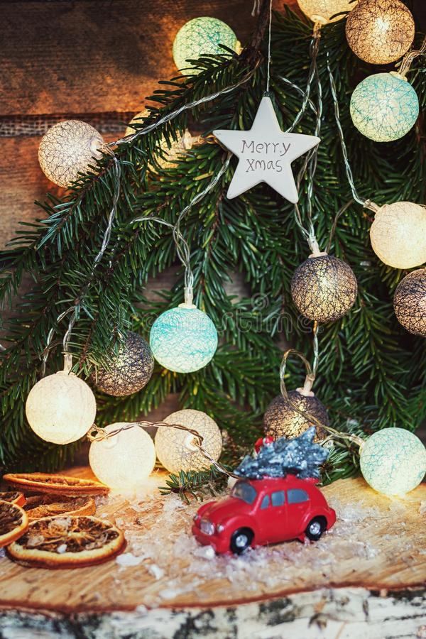 Small red car in front of a Christmas branch decorated with illuminated christmas balls. Zaandam, Netherlands, January 8, 2017: Small red car in front of a royalty free stock photo