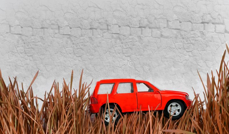 Small red car in the grass against the wall background royalty free stock images