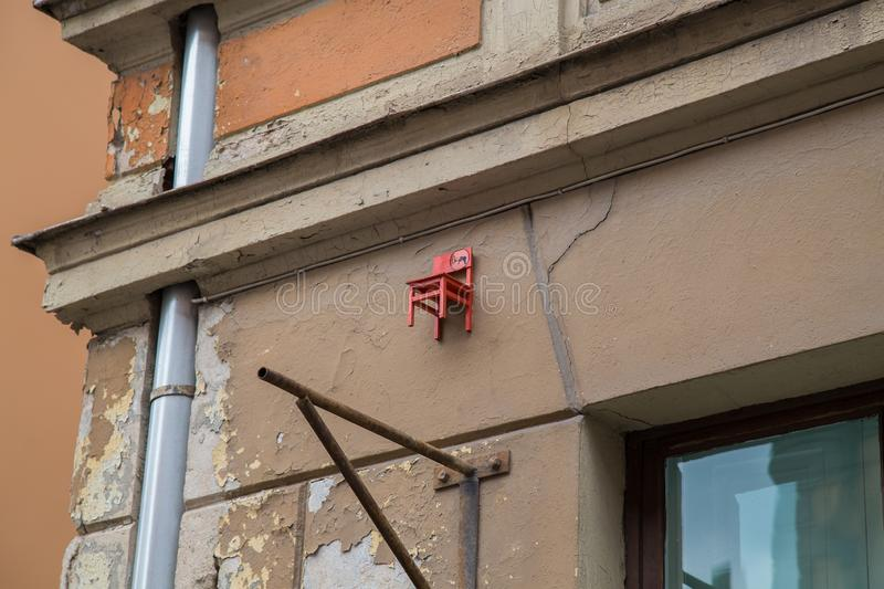 Small red chair on the building in Riga, Latvia. Small chair on top of the building in Riga, Latvia. Building is located in old town in Riga stock photos