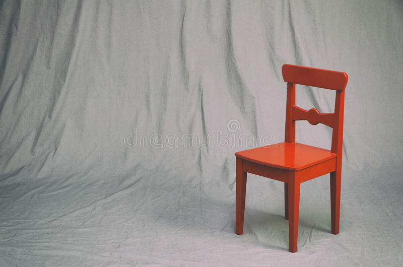 Small red chair. On a grungy gray studio background. vintage filter effects stock photo