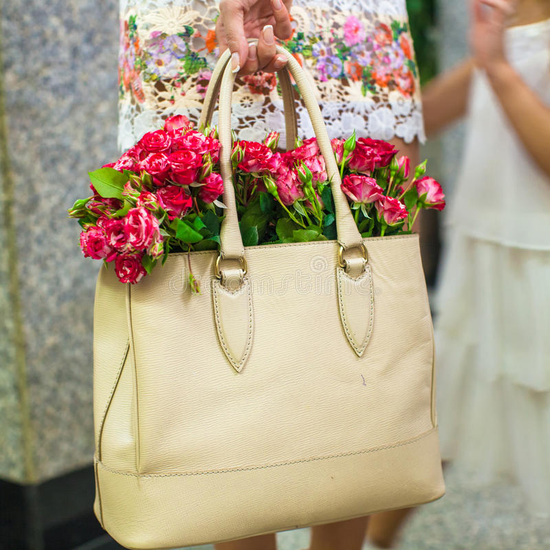 Small red charming flowers in fashion women's bag royalty free stock photos