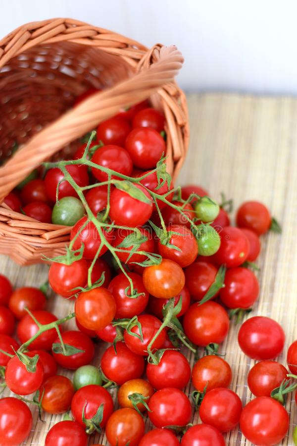 Small red cherry tomatoes in a wicker basket in a rustic style stock photos