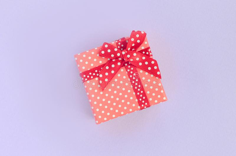 Small red gift box with ribbon lies on a violet background. Minimalism flat lay top view royalty free stock images