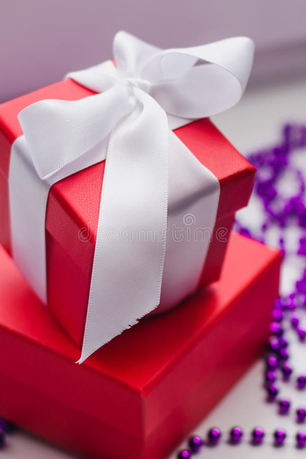 Small red gift boxes tied with a white ribbon and purple Christmas beads on a light background stock images