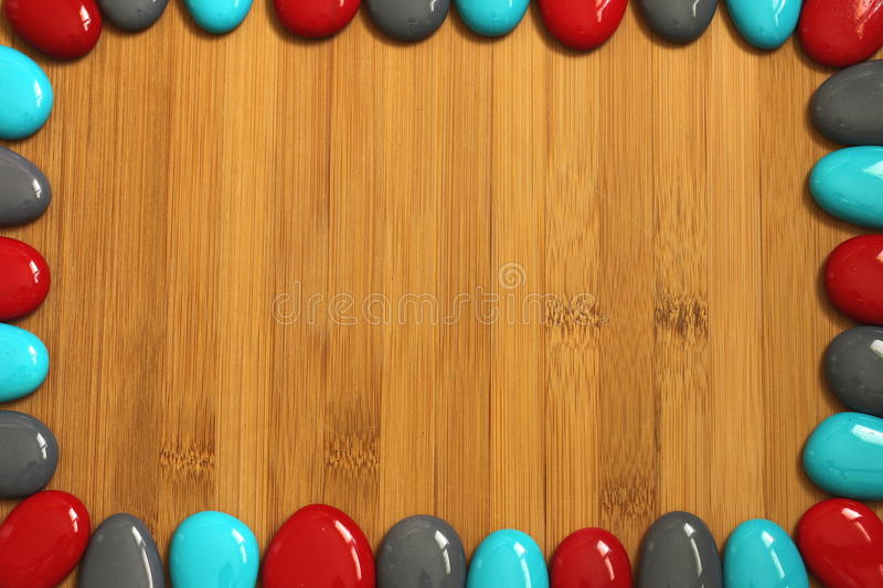 Small red gray and blue pebbles arranged all around a brown bamboo wood floor with an empty space to write a message royalty free stock images