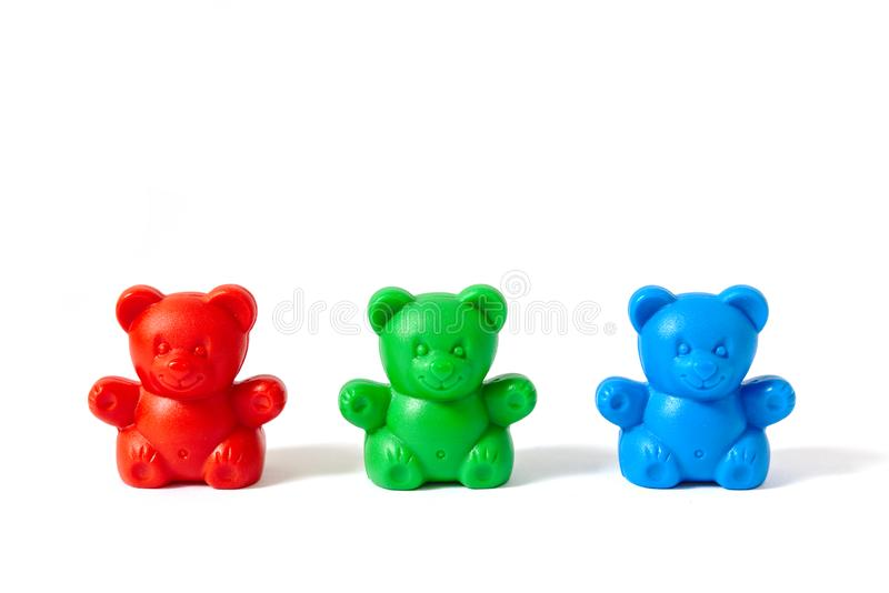 Red, green and blue plastic toy bears isolated on white background. Small red, green and blue plastic toy bears isolated on white background royalty free stock images