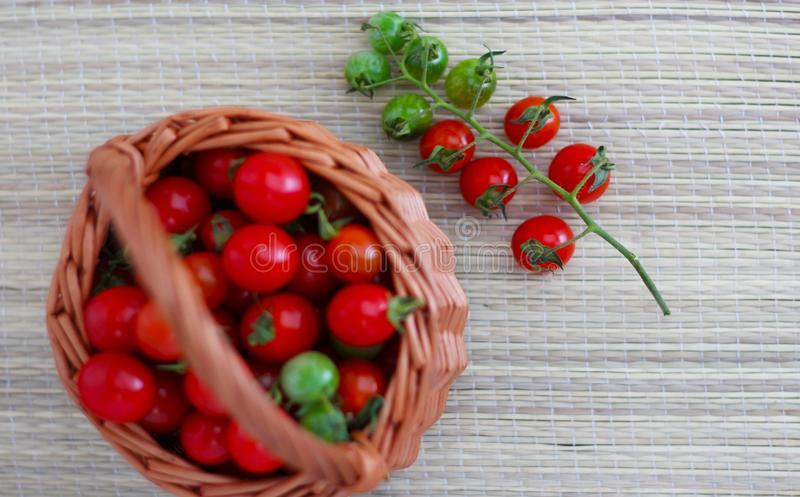 Small cherry tomatoes lie on a bamboo napkin and in a basket royalty free stock photography