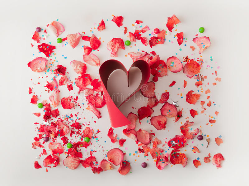 Small red heart made from red ribbon, on white background with rose petals . Composition for themes like love, valentine`s day, ho royalty free stock images