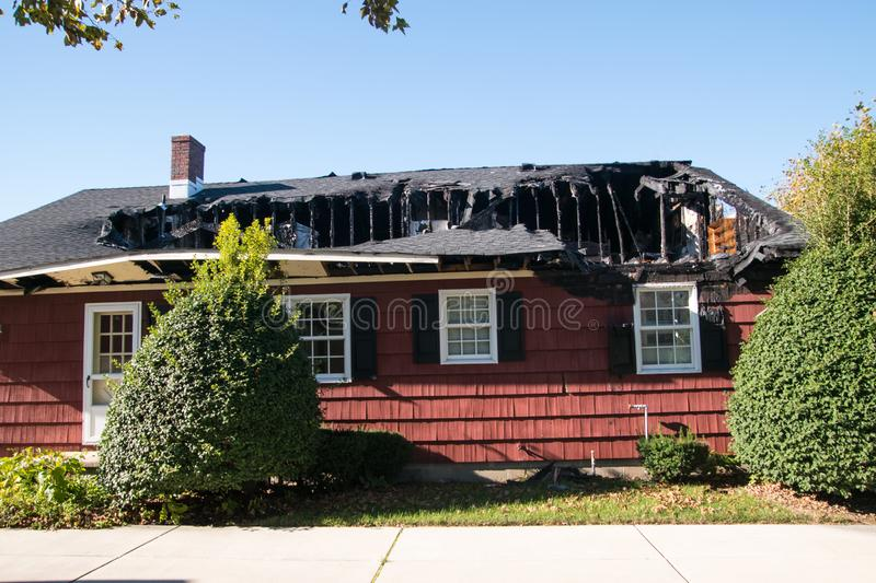 Small red house with roof and top floor destroyed by fire. stock photo