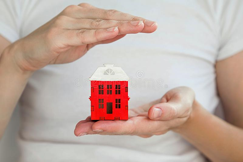 Small red house in women`s hand, one hand protects the roof of the house. stock images