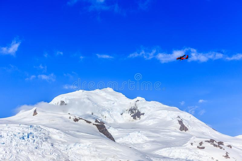 Small red plane flying among clouds over snow peaks and glaciers. Hald Moon island, Antarctic peninsula royalty free stock photos