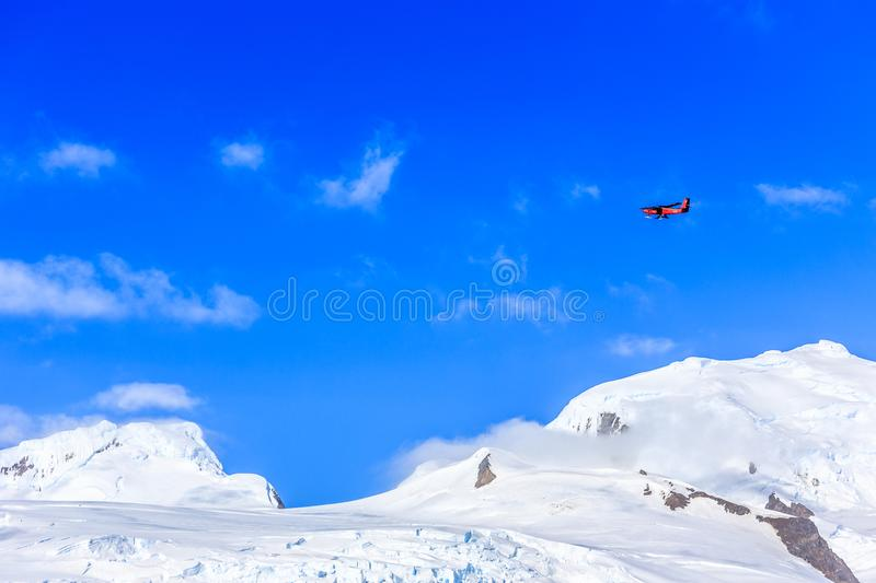 Small red plane flying among clouds over snow peaks and glaciers royalty free stock photos