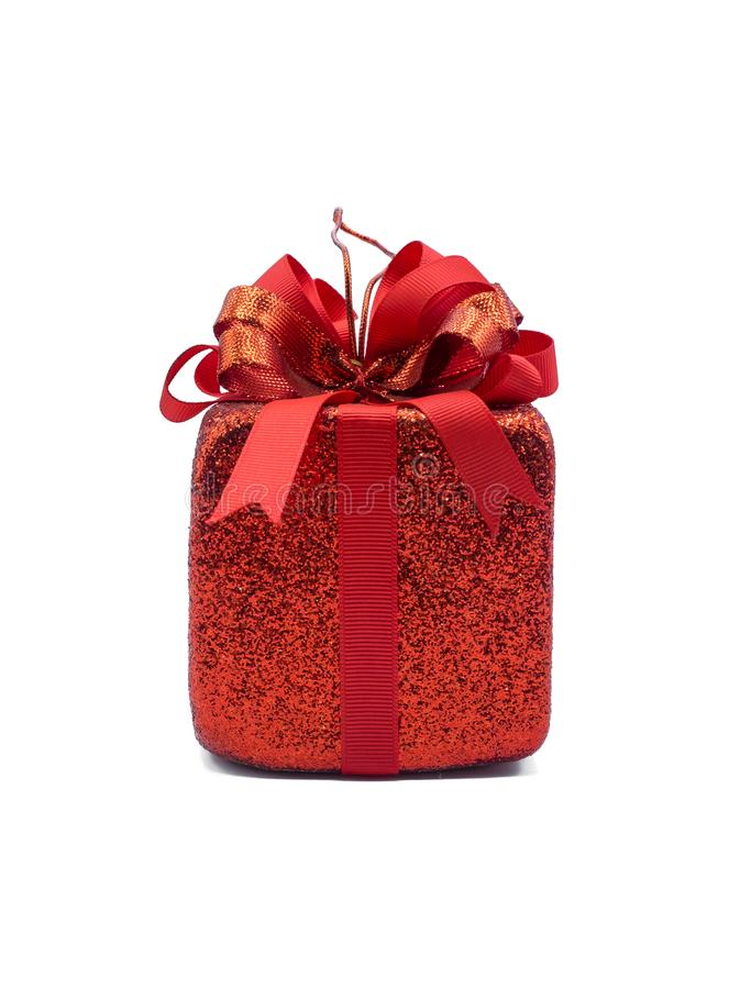 A small red present Christmas ornament for hanging on a Christmas tree. During this festive season. The big red ribbon tie the glitter present. The box of royalty free stock photo