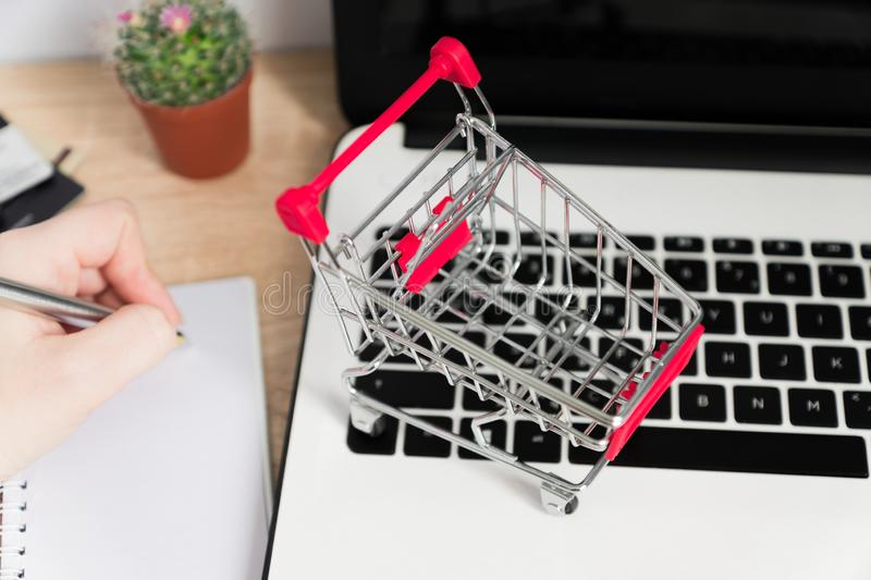 Small red shopping cart or trolley on laptop keyboard, Technology business online shopping concept royalty free stock photos