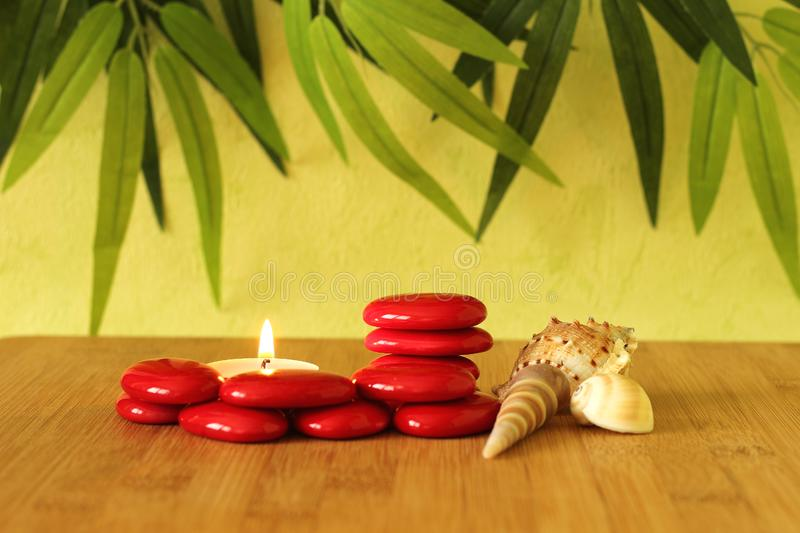 Small red stones arranged in columns in zen lifestyle with a candle and beach shells on bamboo wood floor and green foliage backgr. Red stones arranged in stock image
