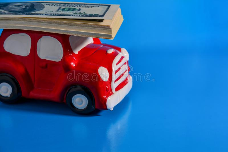A small red toy car carries on the roof a stack of paper banknotes, blue background. The concept of costs for maintenance, car royalty free stock photo