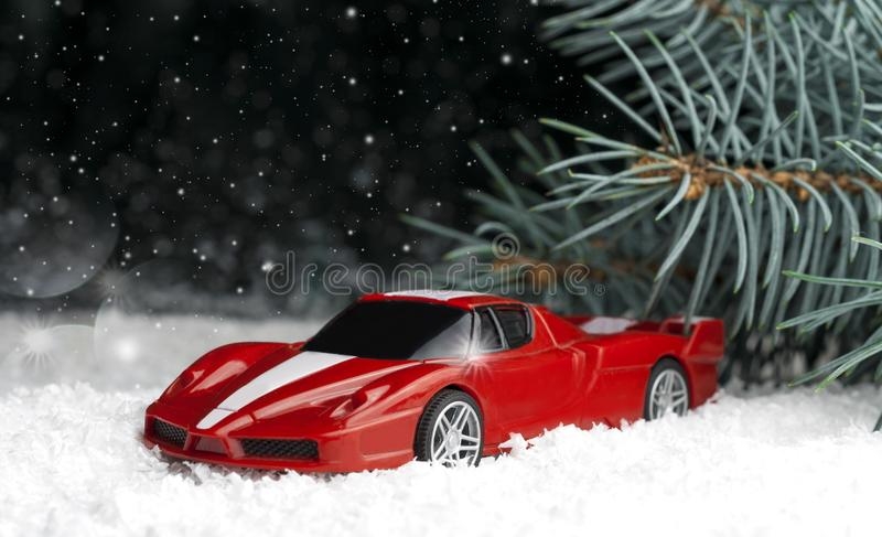 Small, red, toy car in the snow near the fir-tree. Small, red, toy car in the snow near the fir tree, on a dark background royalty free stock photo
