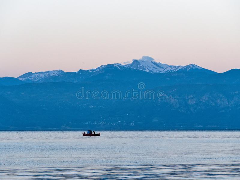 Small Red Greek Fishing Boat and Snow Capped Peloponnese Mountains, Greece. A small red traditional wooden Greek fishing boat, or caique, early morning trawling stock photography