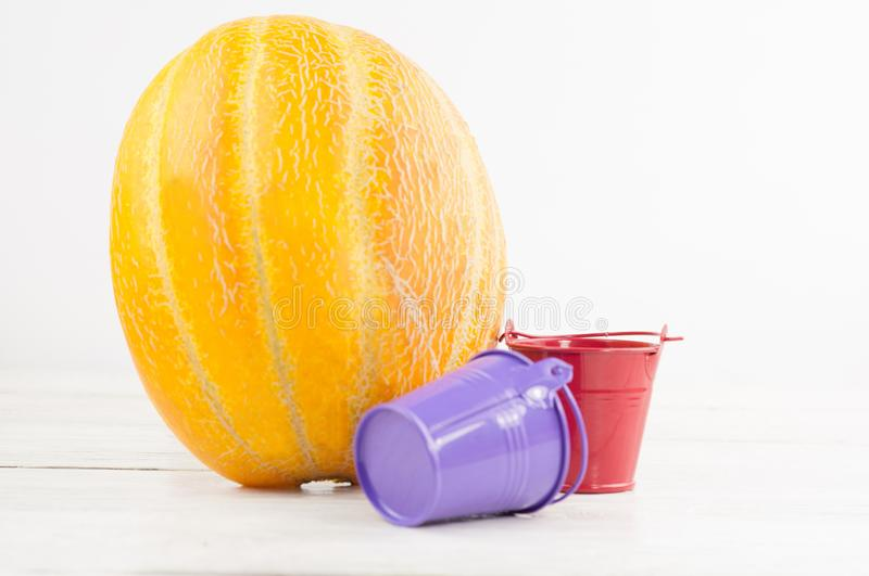 Small red and violet metal buckets and orange watering pot beside whole fresh ripe melon. On old rustic white wooden background royalty free stock photos