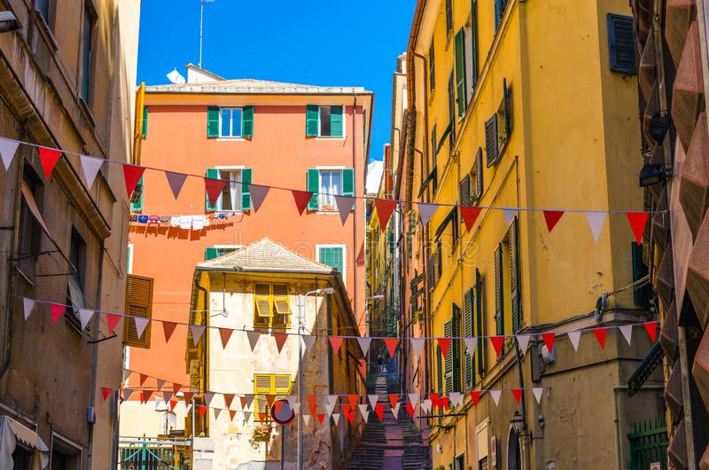 Small red and white flags hang above street with colorful multicolored buildings with shutters on windows in historical centre of. Old european city Genoa stock image