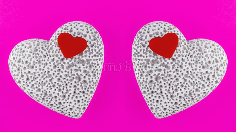 Small red wooden heart lying on a large white stone heart with pores. Mirroring. royalty free stock photography
