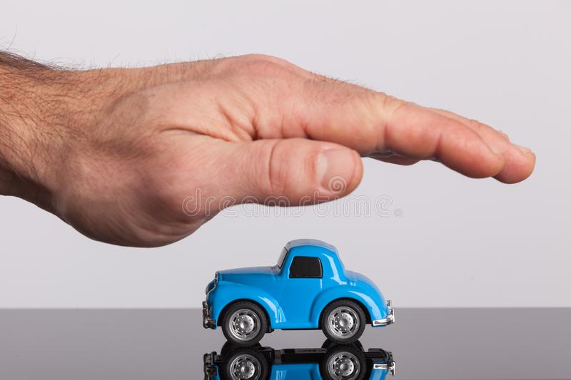 Small retro, blue car covering by male hand. Protection, car insurance stock photos