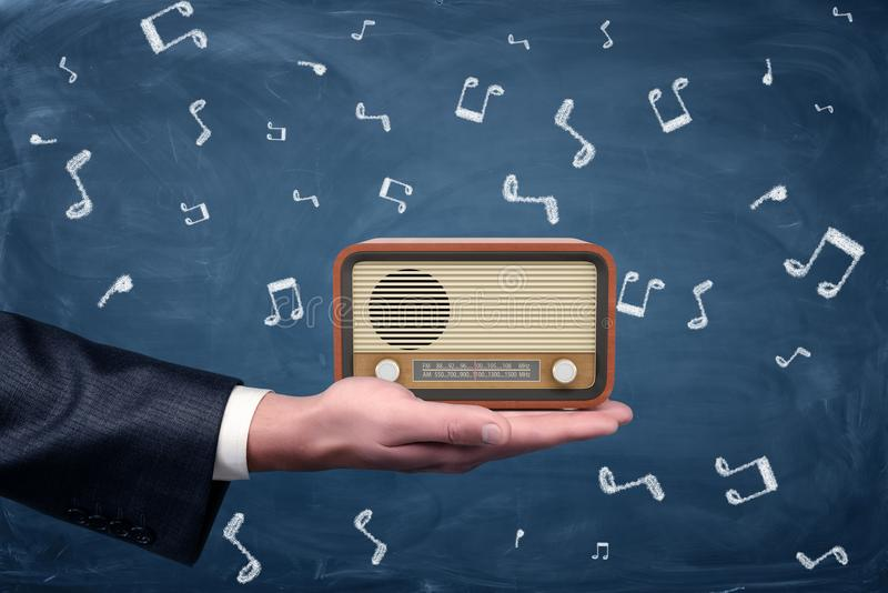 A small retro radio set with brown housing and yellow front stands on a businessman`s palm on blackboard background. stock images