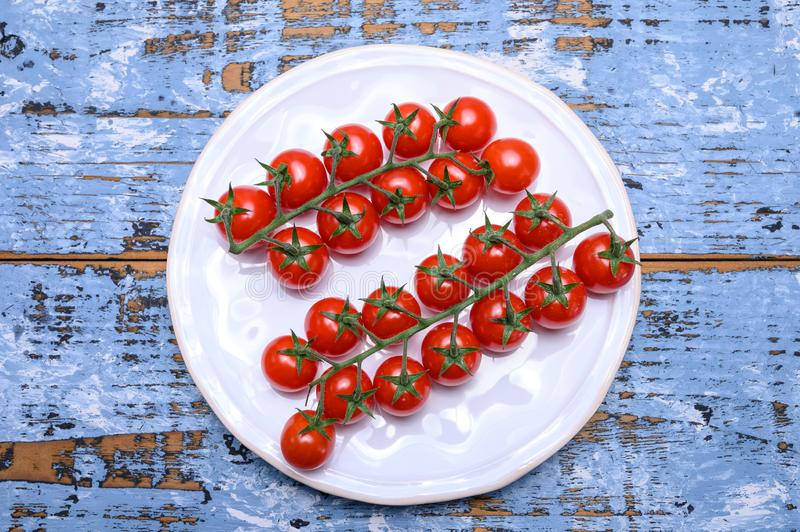 Small ripe red sweet cherry tomatoes on twig stock photo