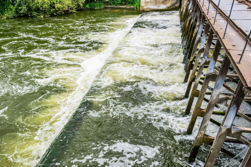 On a small  river dam. On a small river dam. Water falls down, splashes and foam royalty free stock images