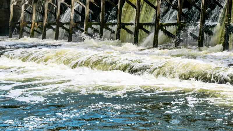 On a small river dam. Water falls down, splashes and foam royalty free stock photos