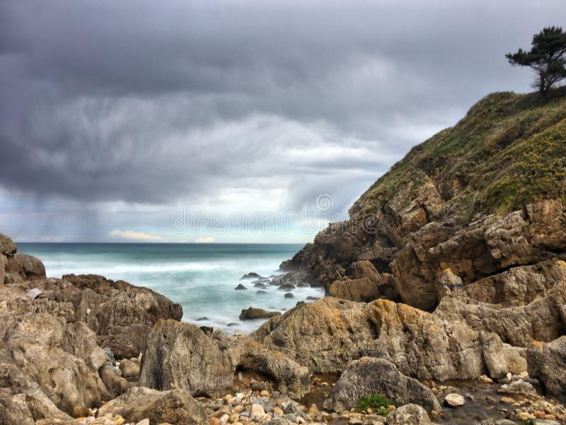 Small river empties into the sea. Between rocks in an unpopulated environment. Asturias stock photo