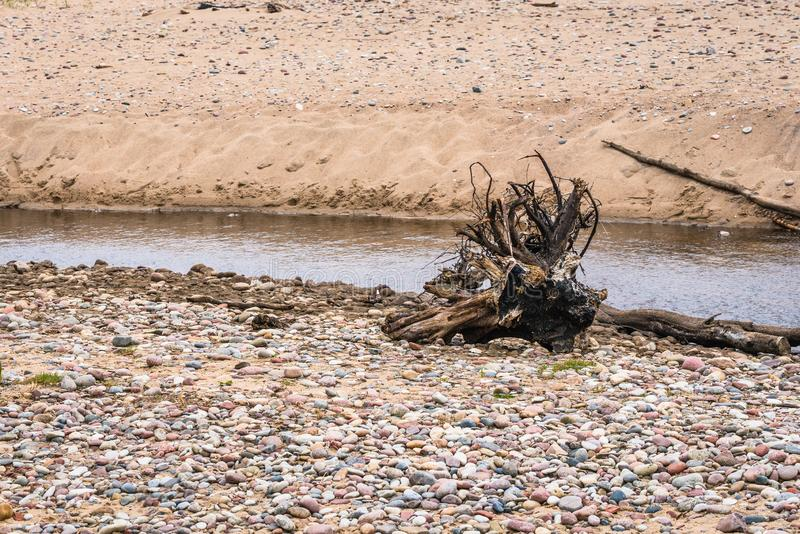 Small river with stump on the rocky shore stock photography
